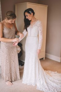 Bridesmaid is helping Rachel to fit in her dreamy wedding gown
