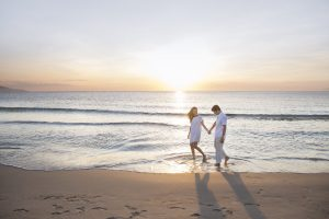 A couple walking hand-in-hand along a sandy beach at sunset.