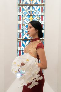 Zoen holding bouquet infront of stained glass