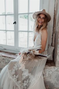 bride in white gown holding dried flowers