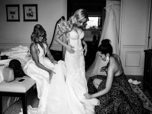 bridesmaid helping Leah to fit in her gown